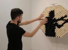 Un jeune homme teste l'oeuvre interactive de Danny Rozin, composée de pompons noirs et blancs